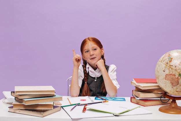 Schattig klein schoolmeisje met sproeten en moderne staartjes in wit overhemd en sarafan heeft idee op paarse geïsoleerde muur