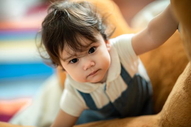 Schattig klein speels meisje dat leert lopen en staan door thuis op de bank te steunen terwijl hij ondeugend wegkijkt