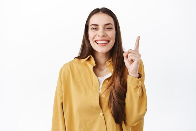 Schattig koket meisje giechelt, glimlacht en wijst met de vinger omhoog, toont advertentie hierboven, top promo-deal, raadt aan om een kijkje te nemen, staande over een witte muur
