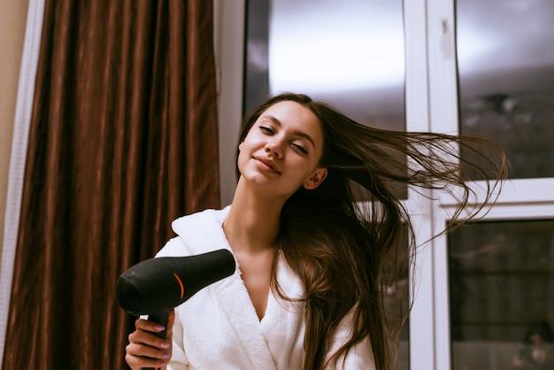 Schattig lachend meisje droogt haar lange haar met een haardroger