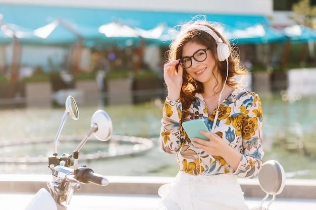 Schattig lachend meisje kijkt met belangstelling, houdt haar trendy grote bril vast en luistert naar muziek