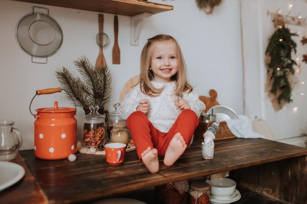 Schattig lachend meisje zit op een houten keukentafel in de kamer ingericht voor kerstmis