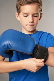 Schattig mannelijk kind bokser aanscherping bokshandschoen rond pols voor de praktijk
