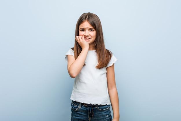 Schattig meisje bijt nagels, nerveus en erg angstig.