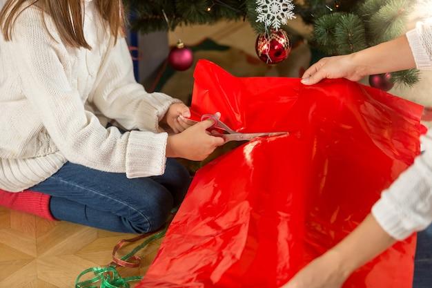 Schattig meisje dat rood papier snijdt om kerstcadeautjes in te pakken