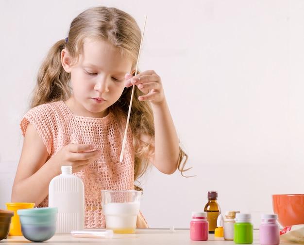 Schattig meisje dat slijmspeelgoed maakt, mazen ingrediënten voor populair zelfgemaakt speelgoed.