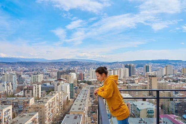 Schattig meisje dat zich voordeed terwijl ze op het balkon van de hoge verdieping van de wolkenkrabber staat met een stadsgezicht erachter.