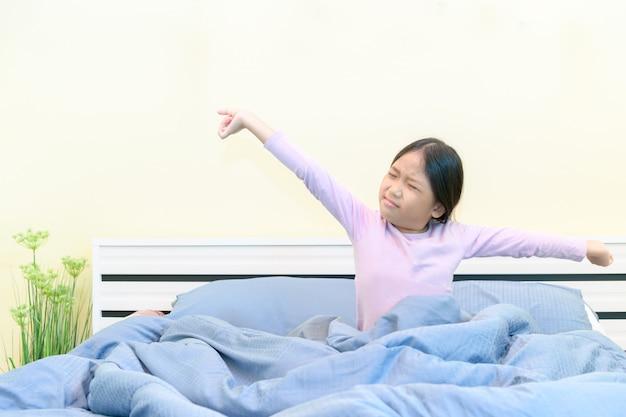 Schattig meisje die zich uitstrekt in bed na het wakker worden,
