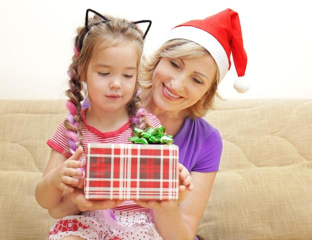 Schattig meisje en grootmoeder met kerstcadeau op de bank thuis