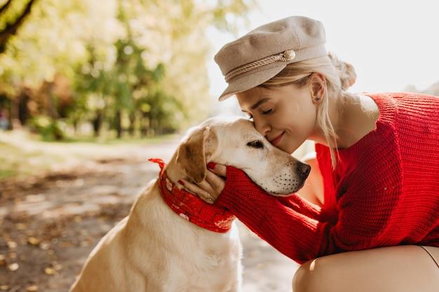 Schattig meisje en haar hond zitten onder groene bomen en felle zon in het park. mooie blondine heeft een goede tijd samen met haar huisdier.