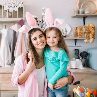 Schattig meisje en moeder in bunny oren knuffelen