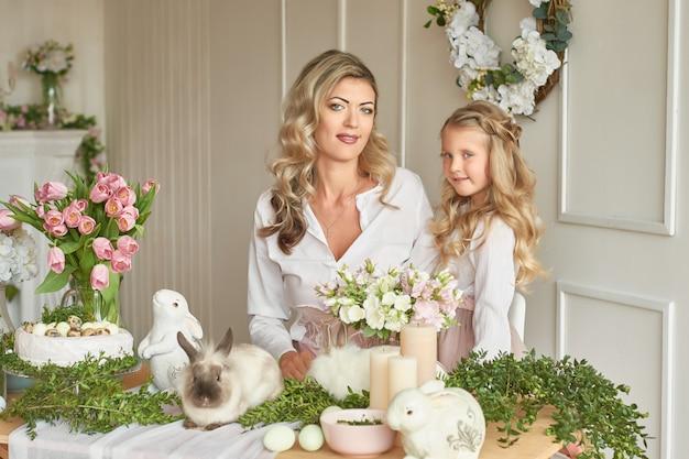 Schattig meisje en moeder spelen met konijnen