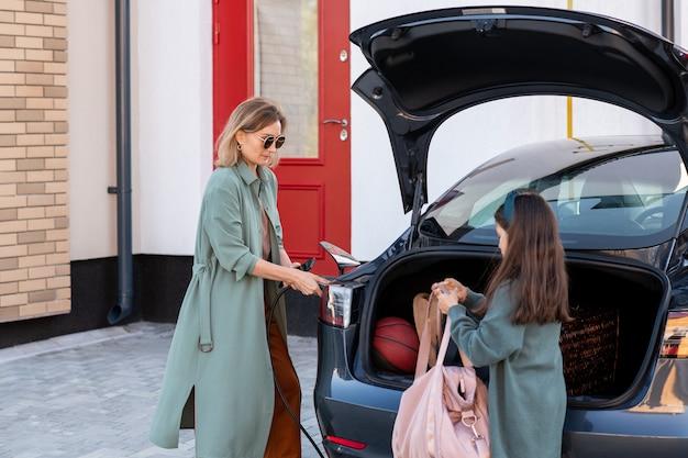 Schattig meisje haalt tas uit kofferbak terwijl haar moeder de auto oplaadt