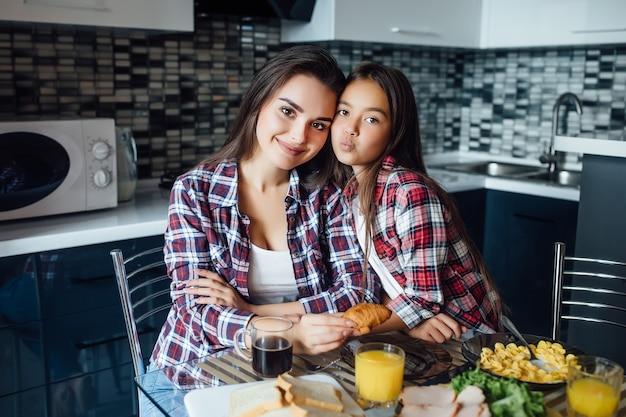 Schattig meisje heeft een gezonde snack met koekjes en melk met haar moeder