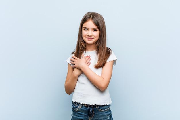 Schattig meisje heeft vriendelijke uitdrukking, palm op borst drukken. liefde concept.