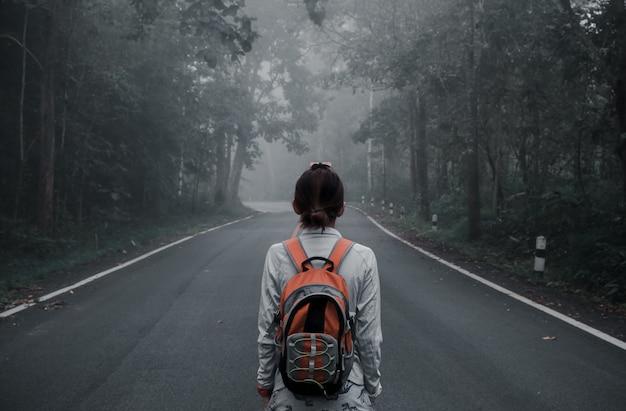 Schattig meisje hipster stijl. ga met je rug in het midden van de weg staan in de vintage stijl van de jungle.