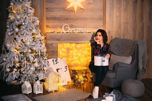 Schattig meisje houdt een geschenk op haar knieën en kijkt naar de cameralens in een kamer bij een kerstboom