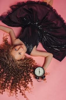 Schattig meisje houdt vintage wekker in zwarte jurk op roze achtergrond in studio black friday concept