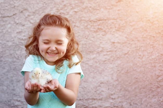 Schattig meisje in een blauw t-shirt met kuiltjes op haar wangen houdt een kip in haar handen en loenst met emotie en genot