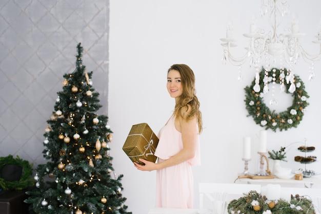 Schattig meisje in een delicate roze jurk met een geschenk in haar handen in de woonkamer, ingericht voor kerstmis en nieuwjaar