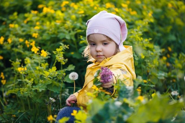Schattig meisje in een geel jasje verzamelt bloemen in een weide. een kind stond in het frisse groene gras tussen de lentebloemen. een klein kind maakt een boeket van de eerste wilde gele bloemen