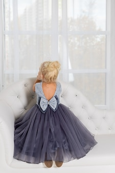 Schattig meisje in een mooie jurk zit thuis op de bank bij het raam. ze is in een mooie jurk. de baby is omgedraaid met haar rug. meisje in grijze jurk in witte lichte zonnige kamer. exemplaarruimte