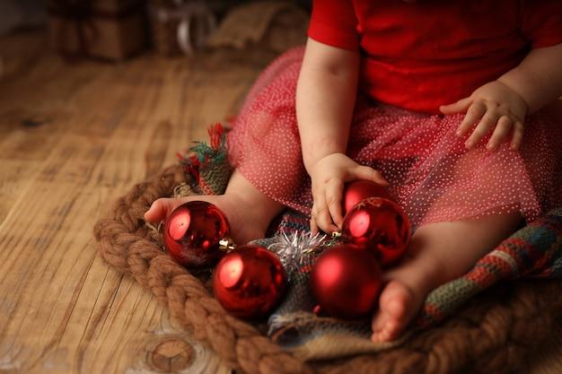 Schattig meisje in een rood kerstkostuum speelt met rode kerstballen