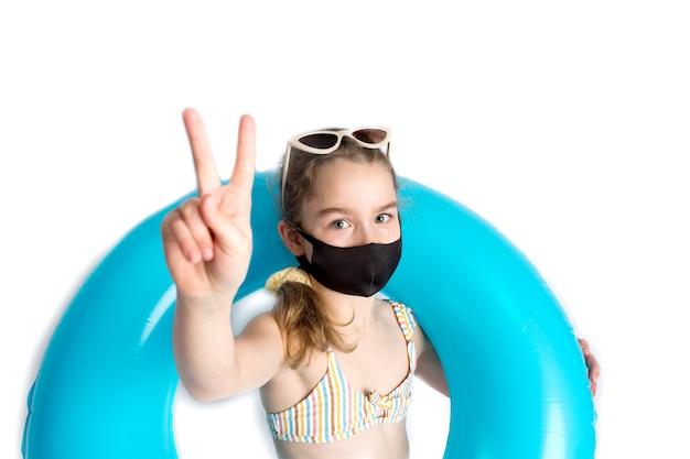 Schattig meisje in een strandbadpak en een opblaasbare turquoise zwemcirkel, in een zwart beschermend covid-19-masker. toont het teken van de overwinning. recreatieconcept tijdens het coronavirus. hoge kwaliteit foto