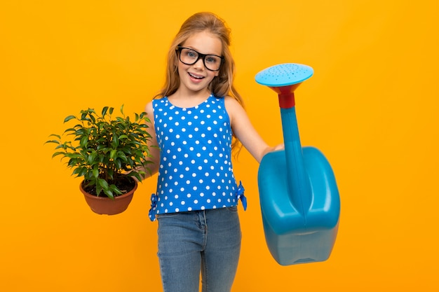 Schattig meisje in glazen heeft een blad plant in haar handen en een gieter op een gele muur