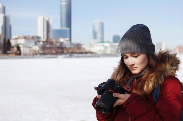 Schattig meisje in grijze gebreide muts tegen de achtergrond van stadsgezicht