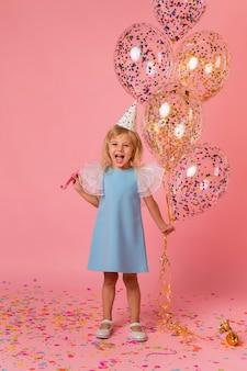 Schattig meisje in kostuum met ballonnen en feestmuts