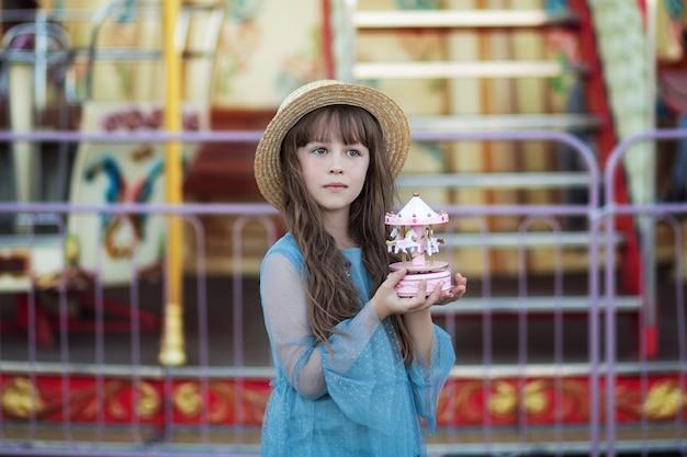 Schattig meisje in pretpark vintage speelgoed carrousel in handen van een klein meisje in hoed Premium Foto