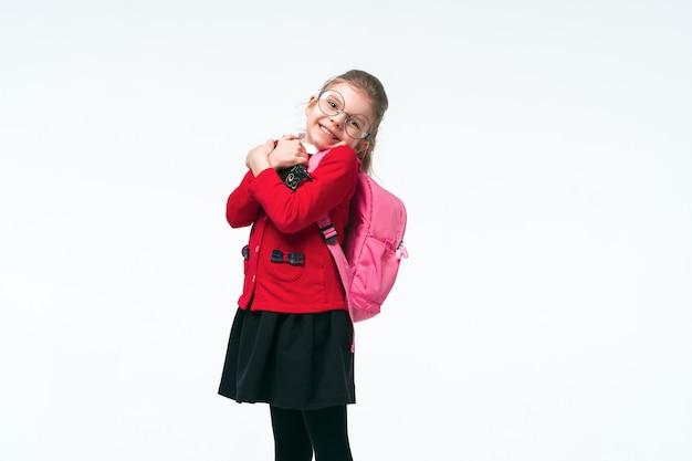 Schattig meisje in rode school jas, zwarte jurk, rugzak en ronde bril knuffels een boek