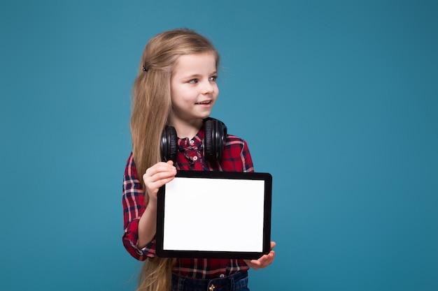 Schattig meisje in shirt en oortelefoons met lang haar houden de pad