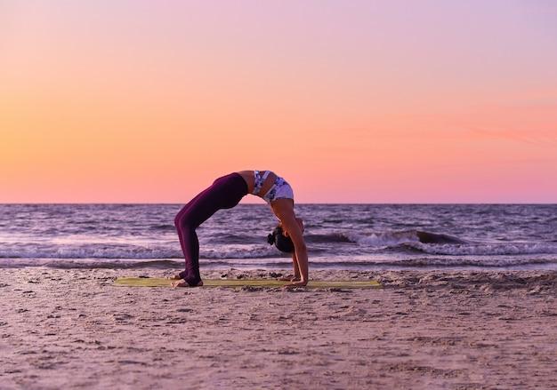 Schattig meisje in sportkleding doet yoga aan zee, bochten, staande in de trog.