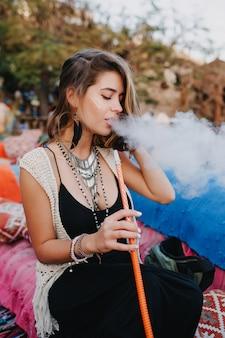 Schattig meisje in zwarte jurk en stijlvolle oorbellen met plezier rookt een waterpijp, zittend op een kleurrijke bank.