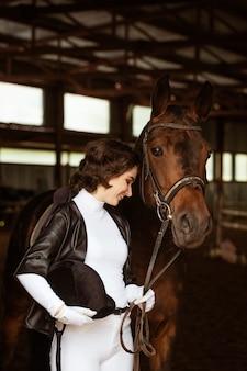 Schattig meisje jockey naast mooi bruin paard schieten close-up mooi jong meisje staat naast ...