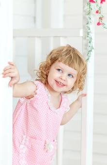 Schattig meisje kijkt naar de straat en lacht van achter de deur