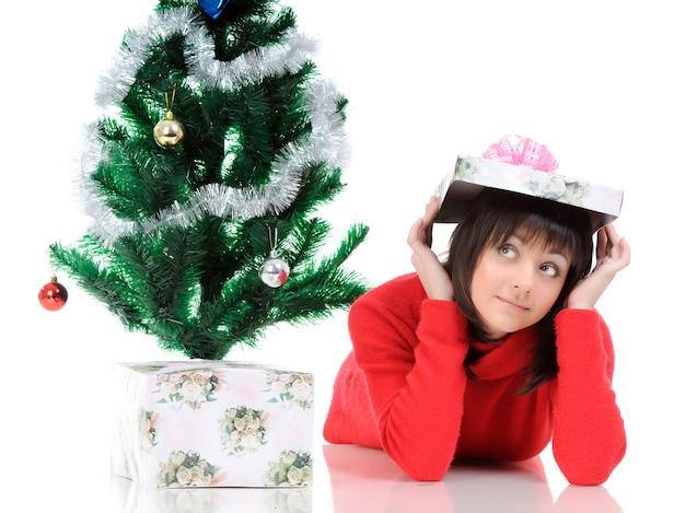 Schattig meisje kijkt op en poseert met een geschenk in haar handen op de achtergrond van de nieuwjaarsboom