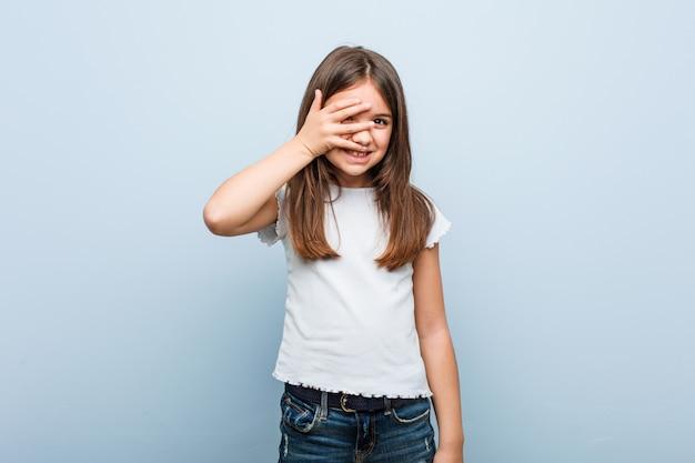 Schattig meisje knipperen naar de camera door vingers, beschaamd bedekkend gezicht.