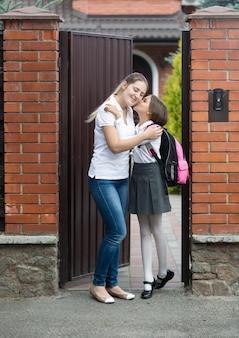 Schattig meisje kust moeder voordat ze naar school gaat