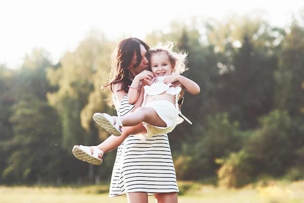 Schattig meisje lacht terwijl ze haar moeder vasthoudt