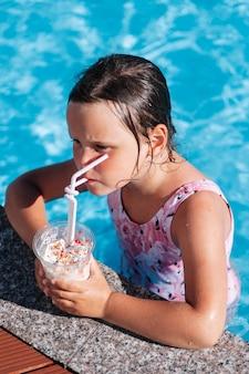 Schattig meisje lest haar dorst en drinkt een milkshake staande op de duikplank van het zwembad relaxi...