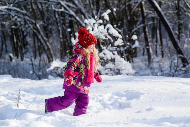 Schattig meisje loopt door de sneeuw