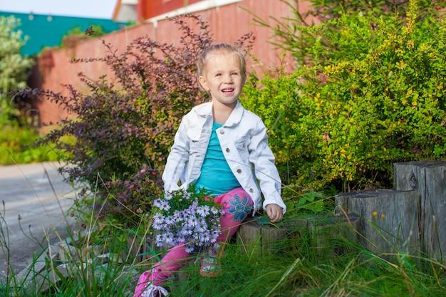 Schattig meisje lopen met een boeket bloemen