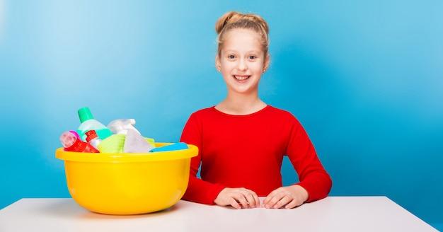 Schattig meisje met een bekken vol met schoonmakers