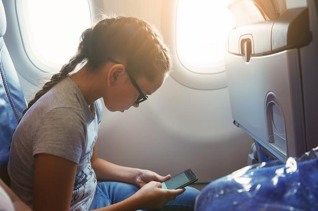 Schattig meisje met een staartje zit in een stoel bij het raam in de cabine van het vliegtuig en communiceert in sociale netwerken op een smartphone.