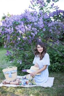 Schattig meisje met een strohoed zit op een plaid en brengt tijd door op een picknick in de lila tuin