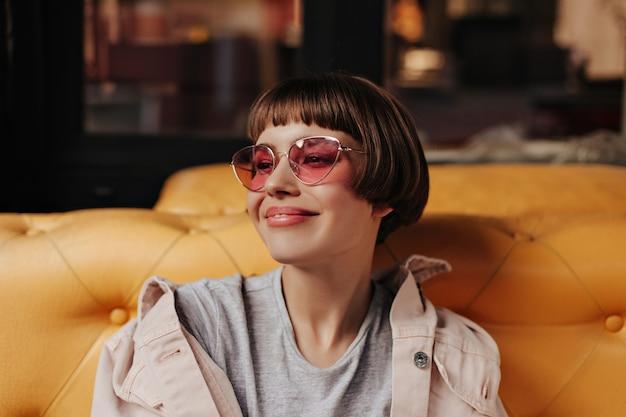 Schattig meisje met felroze zonnebril zittend op gele bank in café