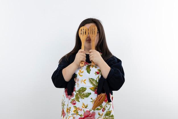 Schattig meisje met het syndroom van down in het kleurrijke schort poseren met houten lepels.